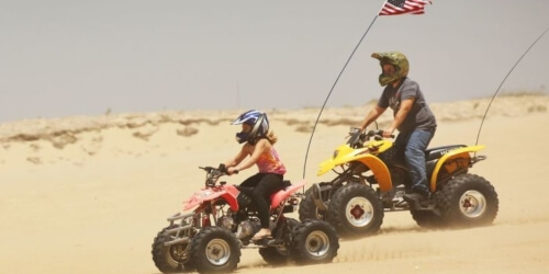 Two ATVs driving in the desert sand