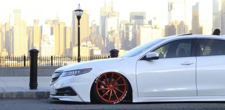 Lowered white car with big orange wheels