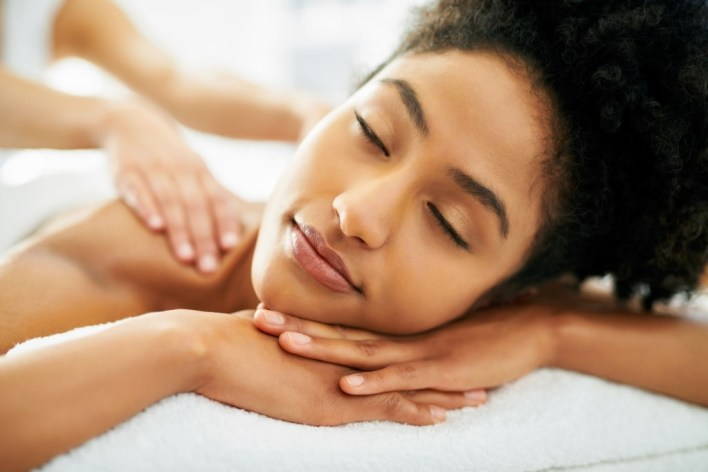 Pain Relief - Shot of an attractive young woman getting a massage at a spa