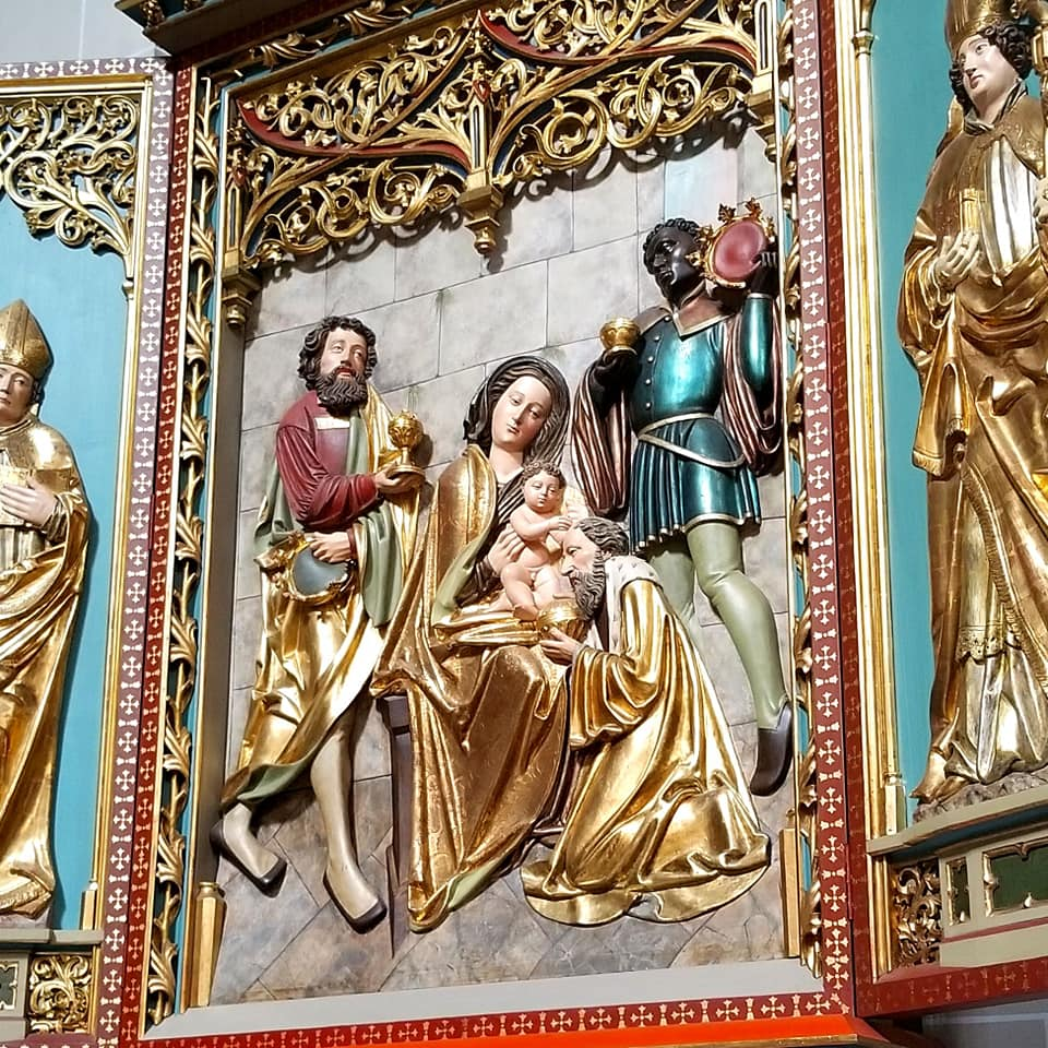 Religious carving at Saint Elisabeth's cathedral in Kosice, Slovakia. There is gold leaf with shades of red and teal. The carving is of one seated woman with someone crying in her lap and two people in the background