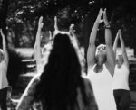 Black and white photograph of a group of people outside practicing yoga.  Their hands are up toward the sky and they are gazing at their hands.  An instructor is standing with her back to the camera, long dark curly hair.  In the background are the people practicing yoga.  There are trees in the background but they are not easy to see because the photo is sharp black and white.