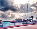 Looking over the harbor in St. George's, Bermuda, with sun coming through the clouds and a few ships in the harbor.