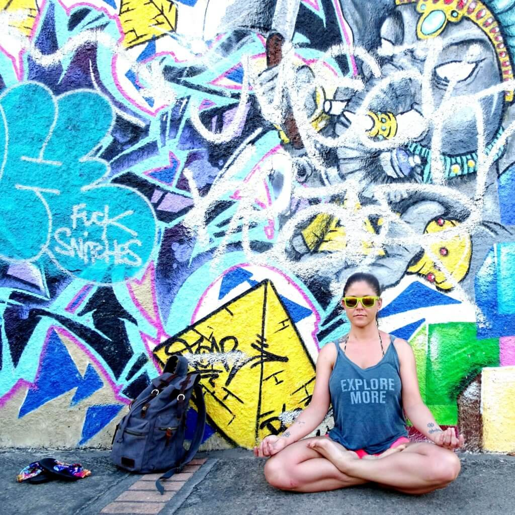 woman sitting in lotus position in front of graffiti art work of ganesh in guadeloupe