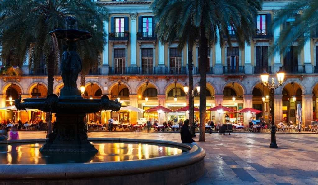 Placa in Barcelona at dusk with lights on and activity all around. A fountain and palm trees in the foreground.