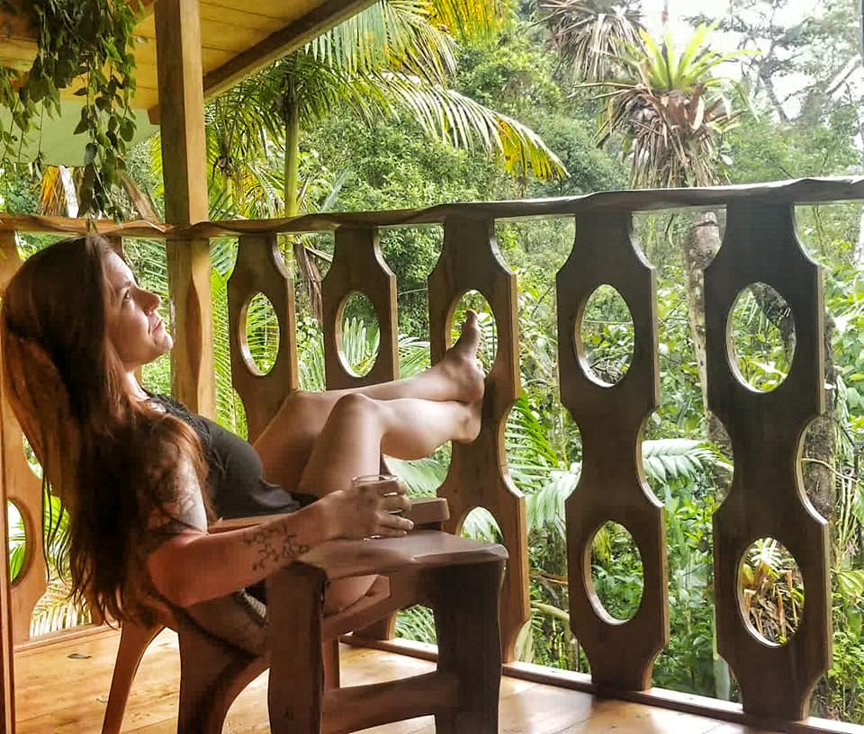 Woman sitting on balcony of treehouse in cloud forest in Ecuador.