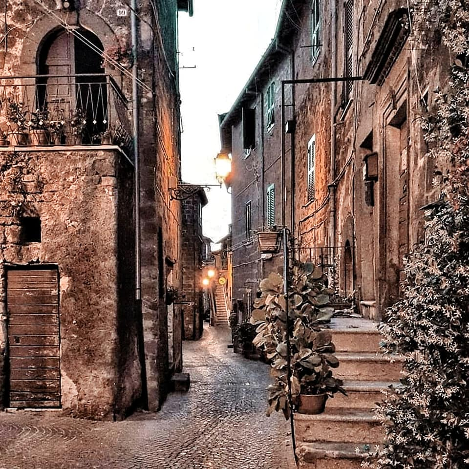 Small medieval village in Tuscia, Italy with narrow cobblestone street running between buildings.