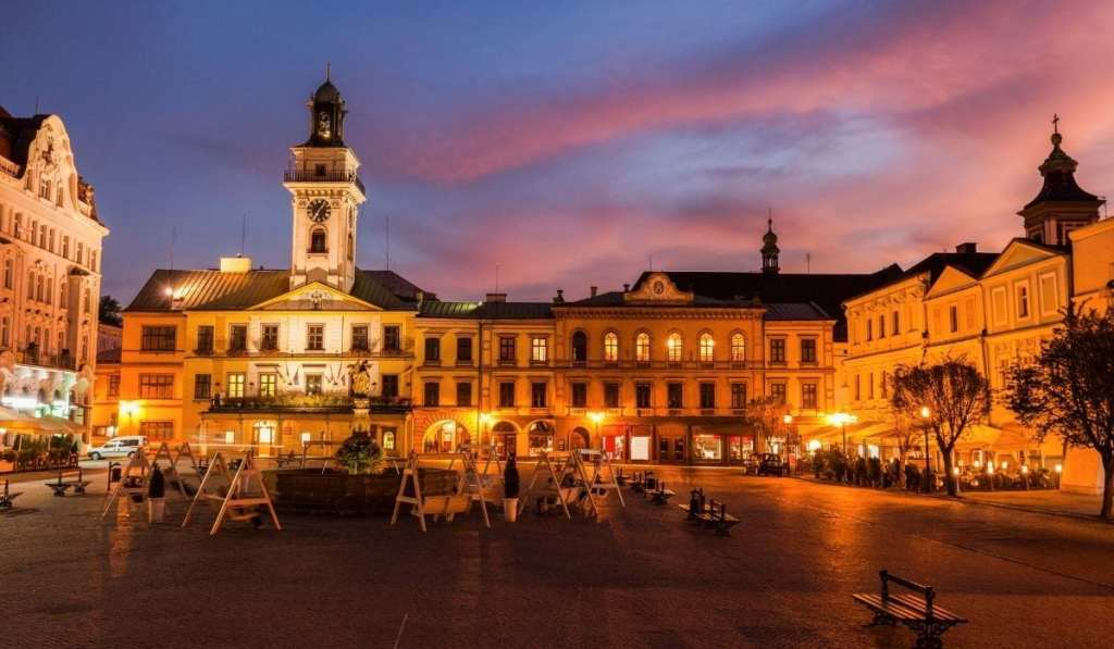 Cieszyn, Poland main square lit up at night with pink and purple skies.