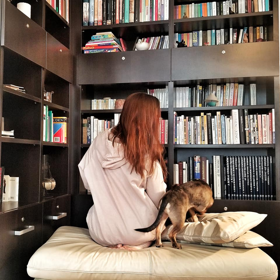 Woman and dog sitting in front of huge bookshelves facing away from camera.