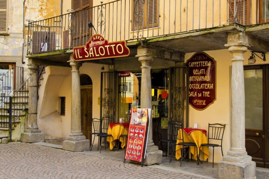 Outer facade of gelateria in Italy with some tables outside that are empty.