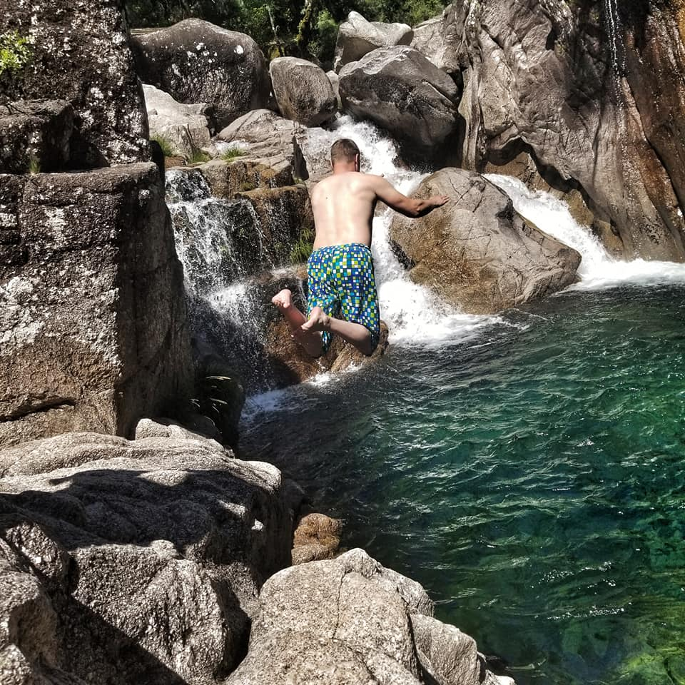 Man jumping off rocks into a clear lagoon with waterfalls in Peneda-Geres, Portugal.
