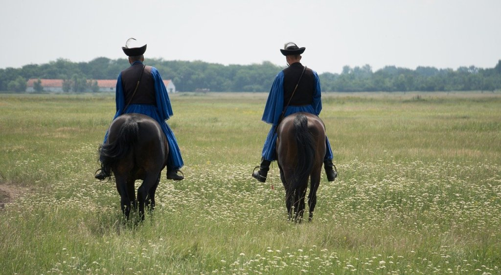 Two Hungarians on horseback riding away in Hortobagy National Park in Hungary, a day trip from Budapest.