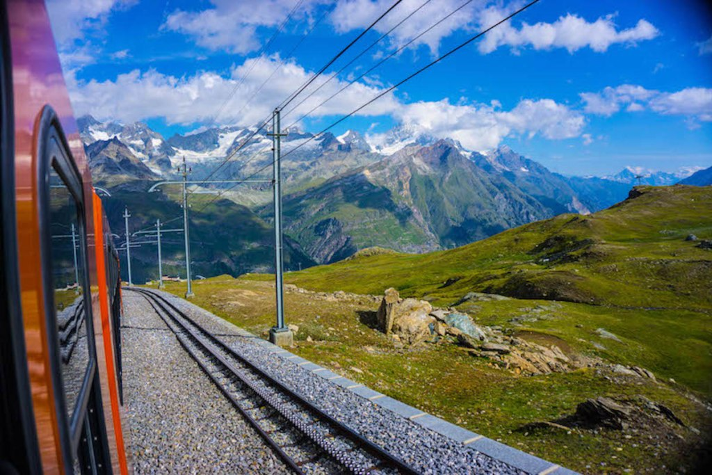 Looking out the window of Gornergrat Bahn, a scenic train ride in Europe overlooking green, snow coered mountains under a blue sky.