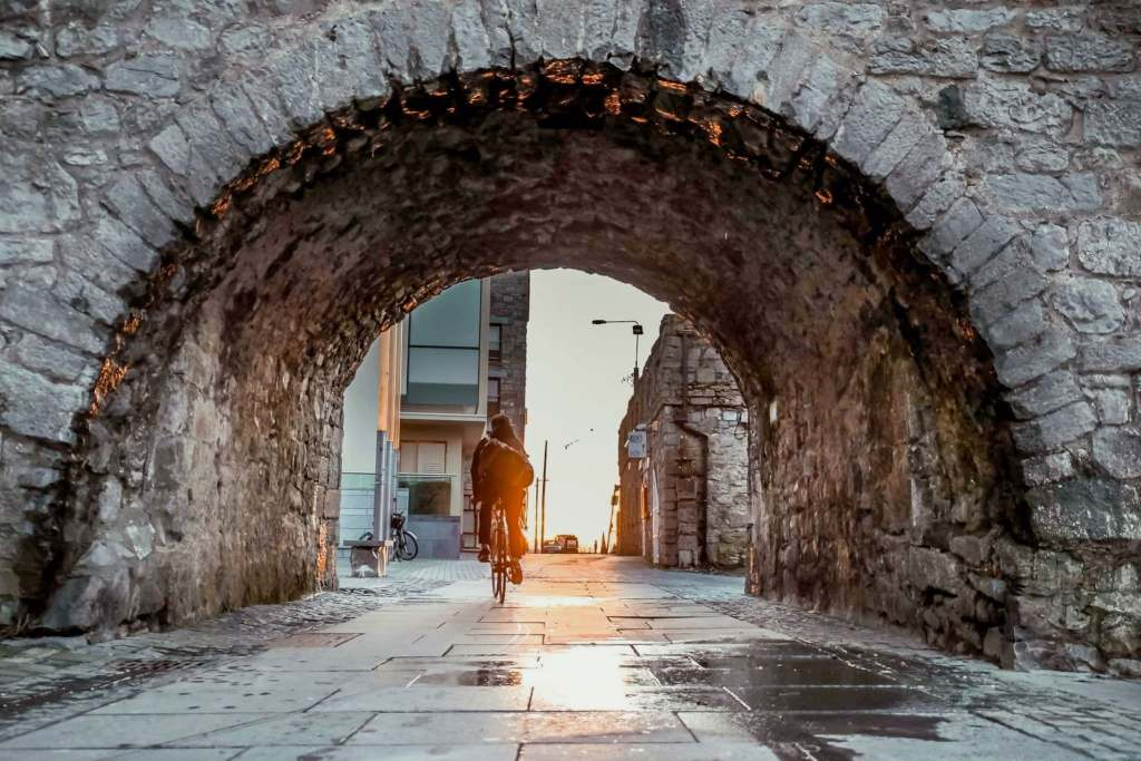 Bicycle riding underneath the Spanish Arch in Galway City, Ireland.
