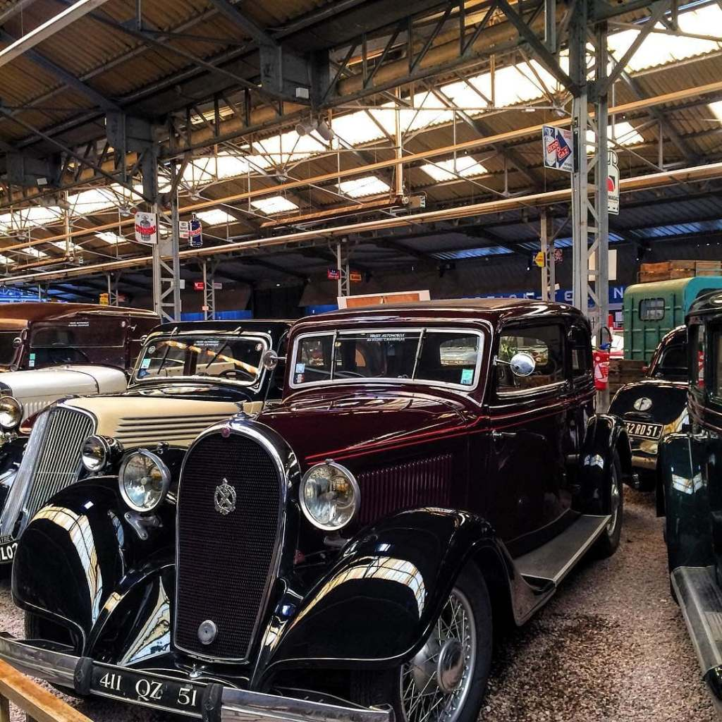 Burgundy-colored classic car surrounded by other cars at the automobile museum in Reims, France.
