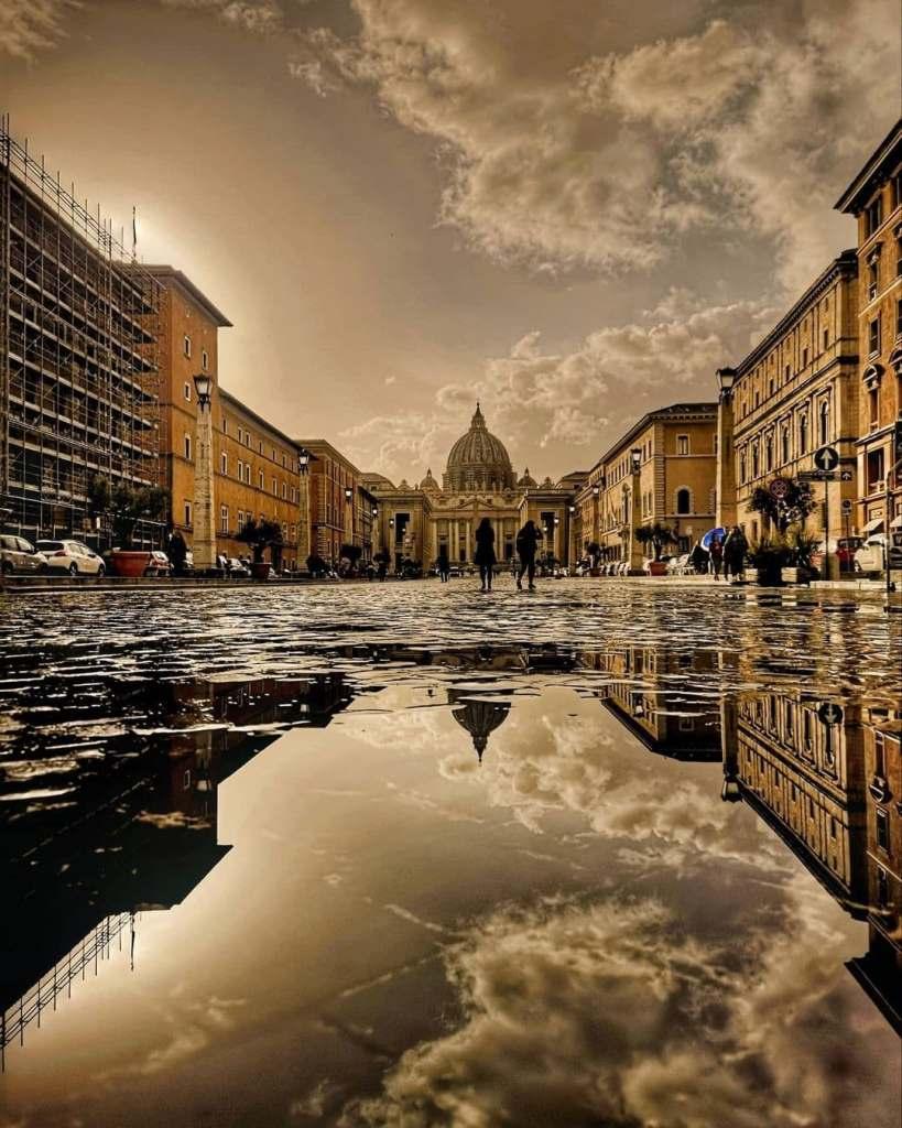 Roman architecture reflected in puddles down via della concilliazione