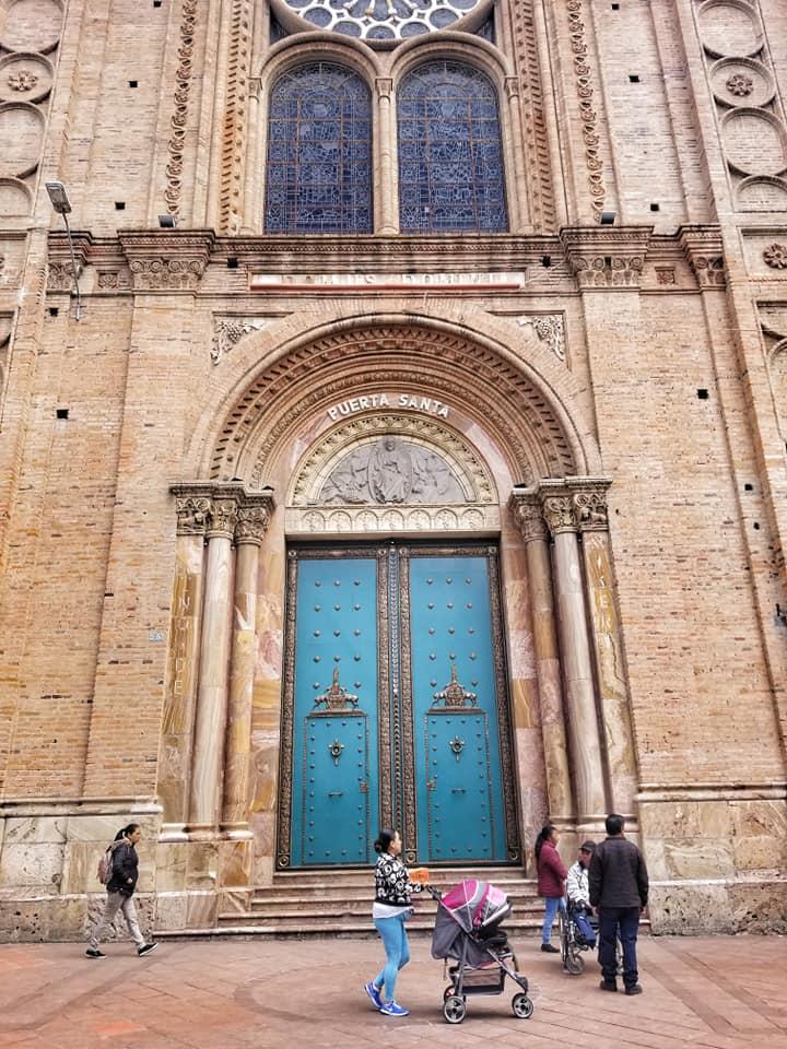 Turquoise door in Cuenca, Ecuador on sand colored building.