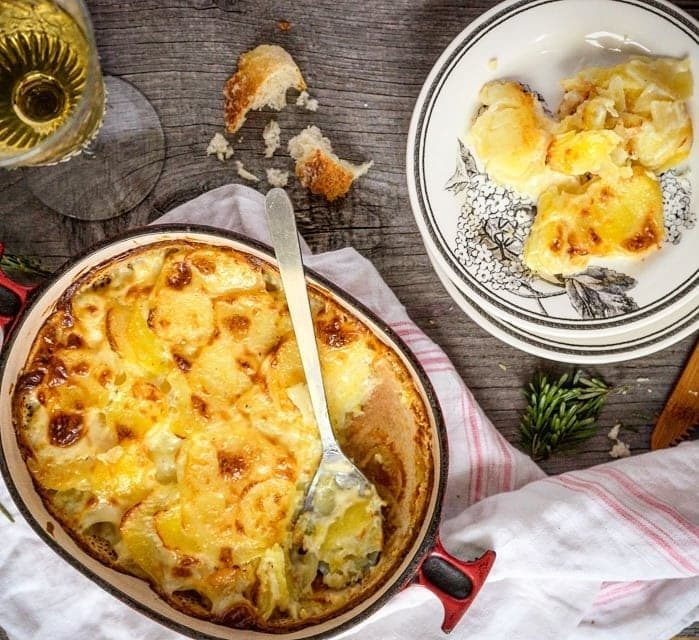 Gratin Dauphinois in a casserole dish alongside a  plate filled with this iconic French food.