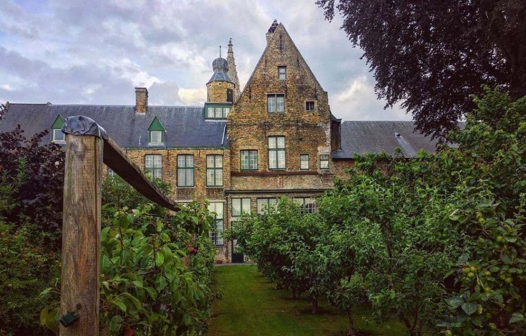 Hof Bladelin in Bruges seen with cloudy skies and through trees and bushes.