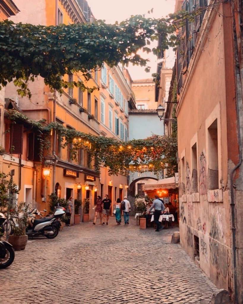 A cobblestone street in Trastevere with ivy and lights hanging overhead, a restaurant on the right and a moped on the left.  One of the most Instagrammable streets in Rome.