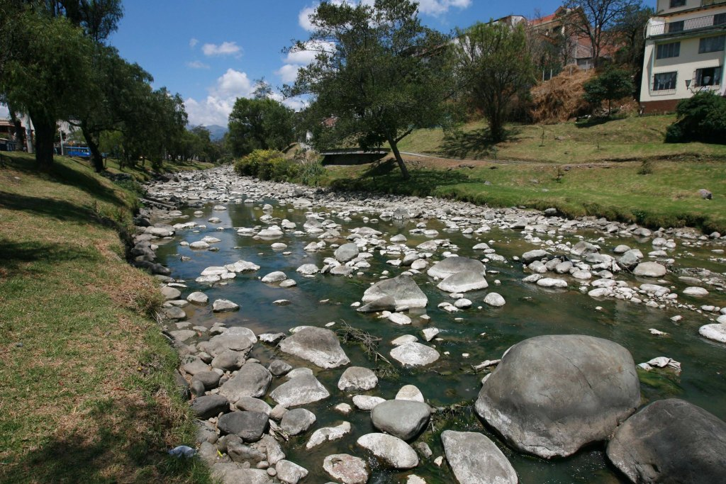 Tomebamba River when the river is low and rocks just out from the surface in Cuenca, Ecuador.