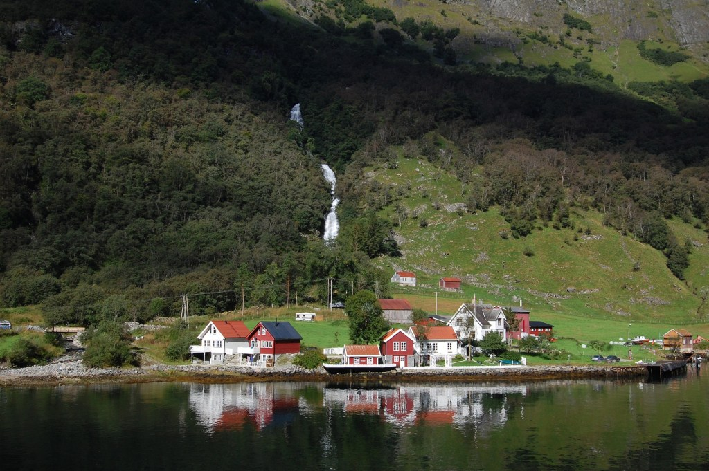 View of red and white lakeside cottages and a cascading waterfall from the Flam Railway.