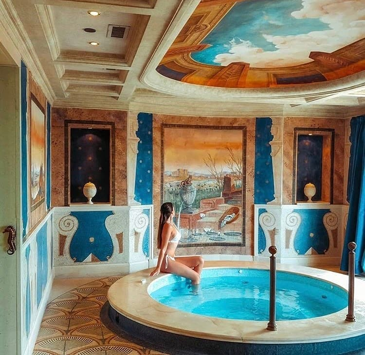 Woman sitting at the edge of a hot tub in a white bikini at the Westin Excelsior Rome, with beautifully painted walls.