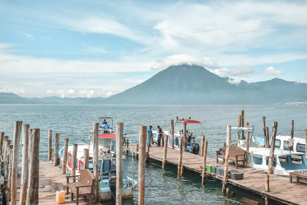 Docks jutting out into Lake Atitlan, Guatemala with mountains in the background.