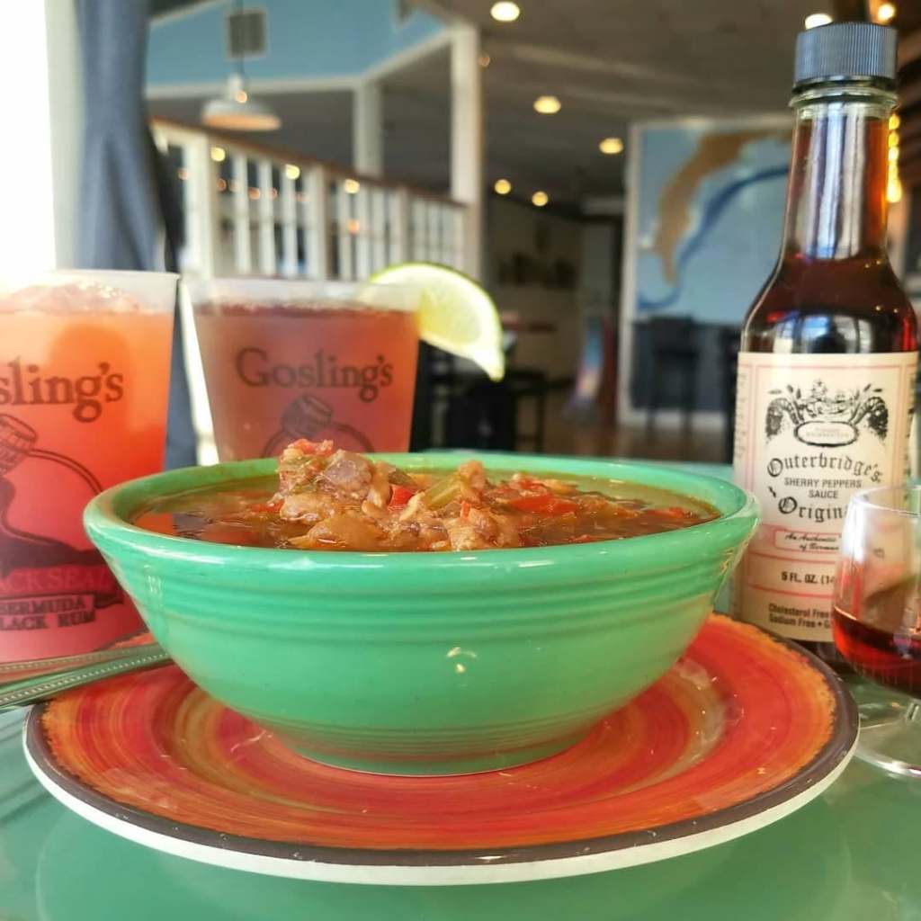 Big bowl of Bermuda Fish Chowder with a couple of Dark'n'Stormies in the background