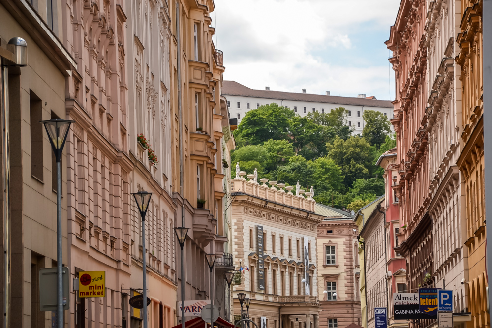 Downtown Brno in Czechia, with pale pink and apricot colored buildings lining a street.  A perfect day trip from Vienna, Austria.