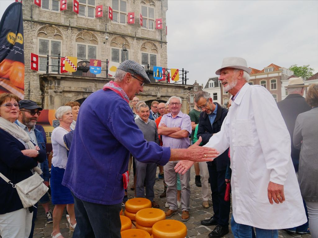 Photo of two Dutch men shaking hands at the cheese market in Gouda, Netherlands.  There are many people around smiling with large circles of Gouda cheese on the ground.