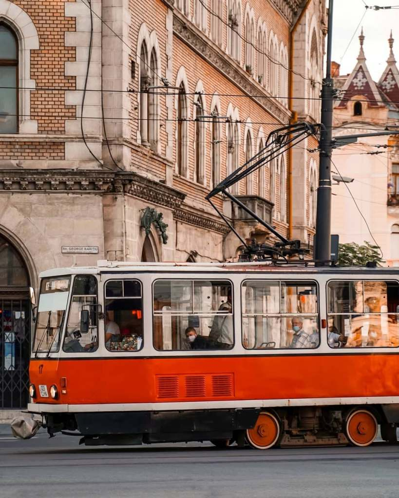 One of Cluj's iconic trolleys with mask-donned people looking out the windows.