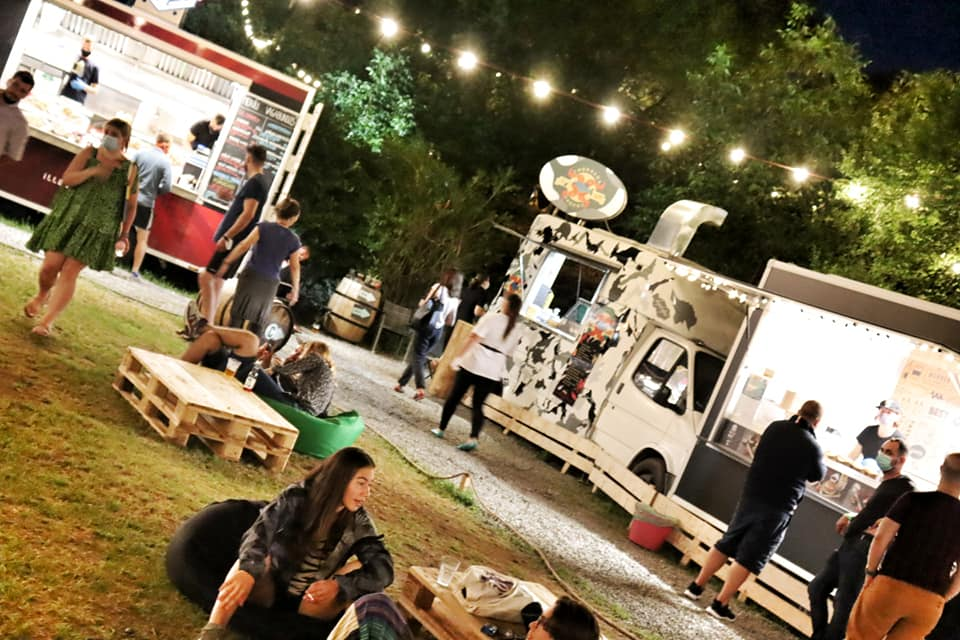 Food trucks at Cetatuia Food Park in Cluj-Napoca, Romania.  People are sitting in bean bags around pallet tables.