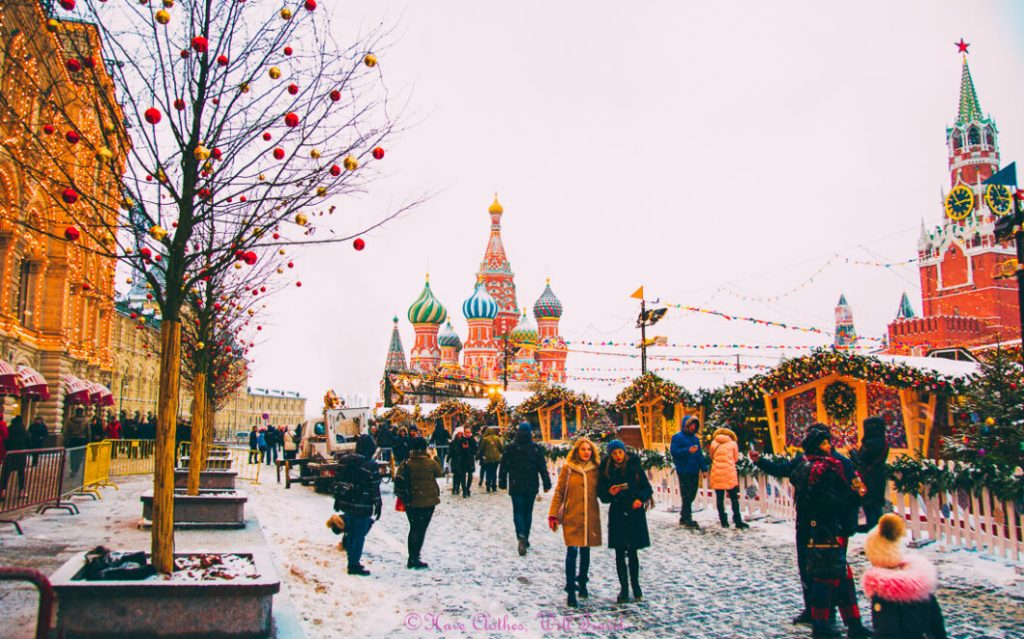 Onion-domed Russian buildings in Moscow while the city is decorated in Christmas lights and ornaments during the Christmas market.  There is a light blanket of snow and people are gathered outside the many stalls.