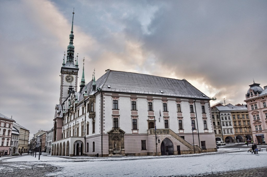 Olomouc, Czechia Town Hall in winter with a light dusting of snow, cloudy skies.