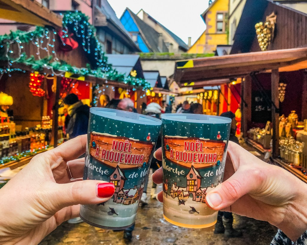 Two hands holding up cups of mulled wine in front of the stalls at the Riquewihr Christmas Market in France.