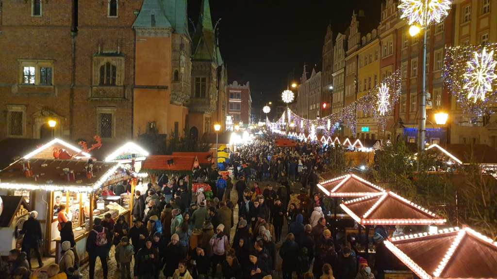 Aerial view of a crowded street in Wroclaw, Poland during the annual Christmas Market.  Booths are lining the streets and many Christmas lights are strung.