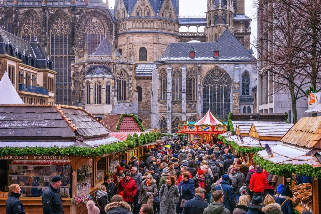 Crowds gather among the wooden stalls under the main Cathedral in Aachen, Germany during the annual Christmas market.