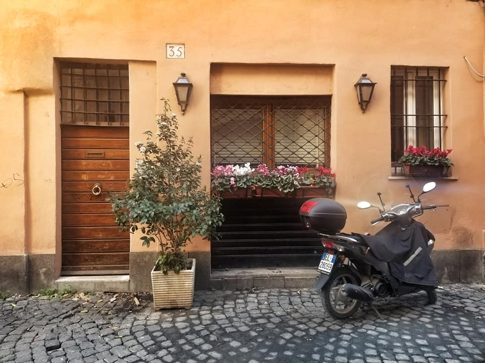 Moped parked outside apartment on cobblestone street in Trastevere, Rome.
