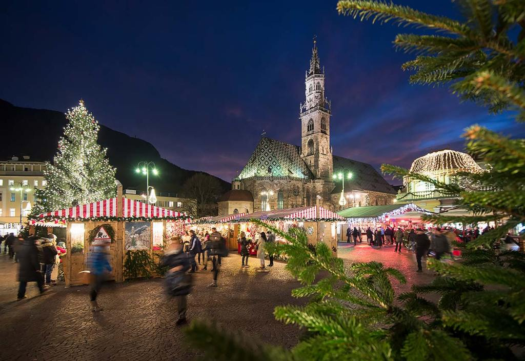 Red and white-topped vendor booths are shown behind a foreground of pine trees in Bolzano Italy during the city's Christmas market.  People are lined up outside the booths.