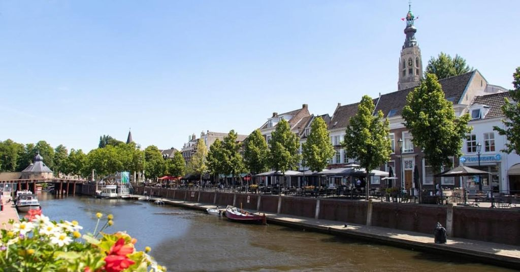 City of Breda in Netherlands with a canal and flowers in the foreground.