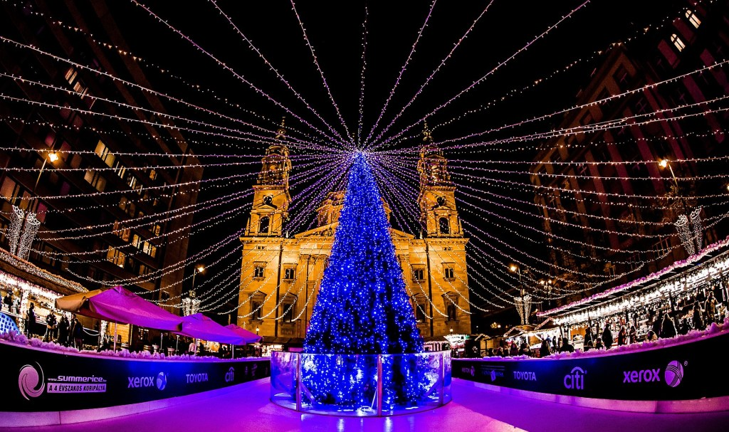 A blue-lit Christmas tree is shown in front of St. Stephen's Basilica in Budapest, Hungary during the annual Christmas market.  There are lights strung from the top of the tree expanding to the perimeter of the market.
