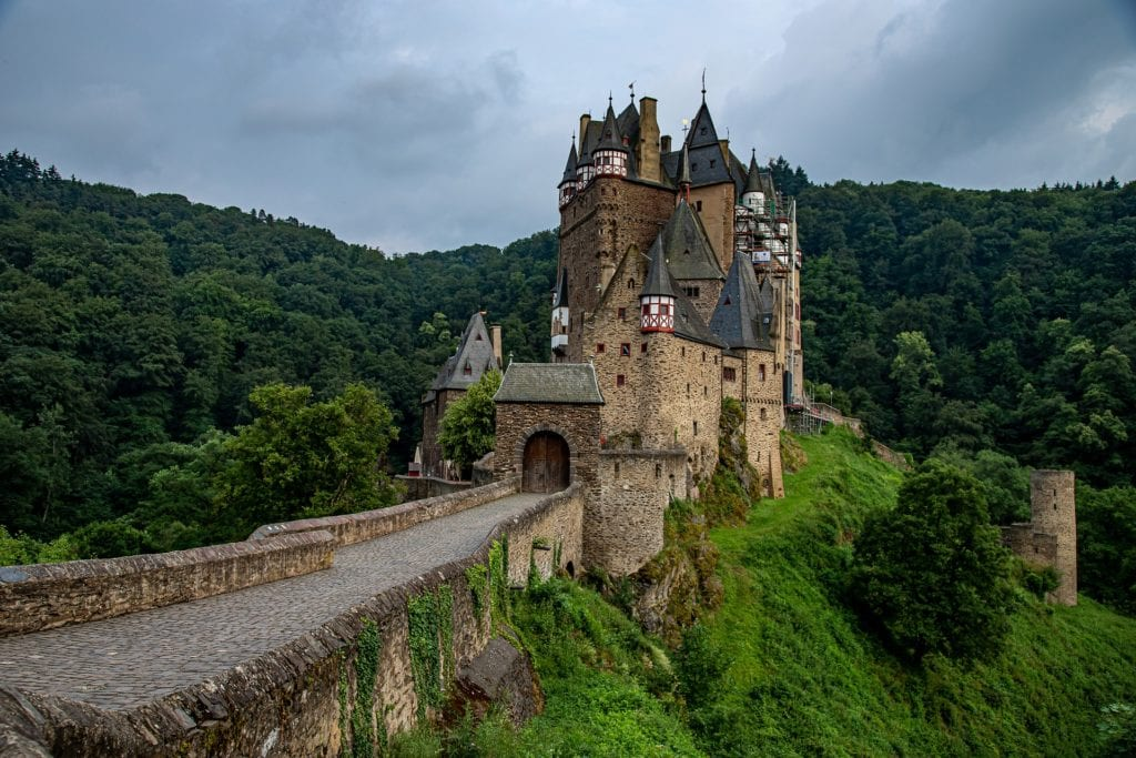Burg Eltz, a magical castle in the forest in Germany surrounded by lush green trees.