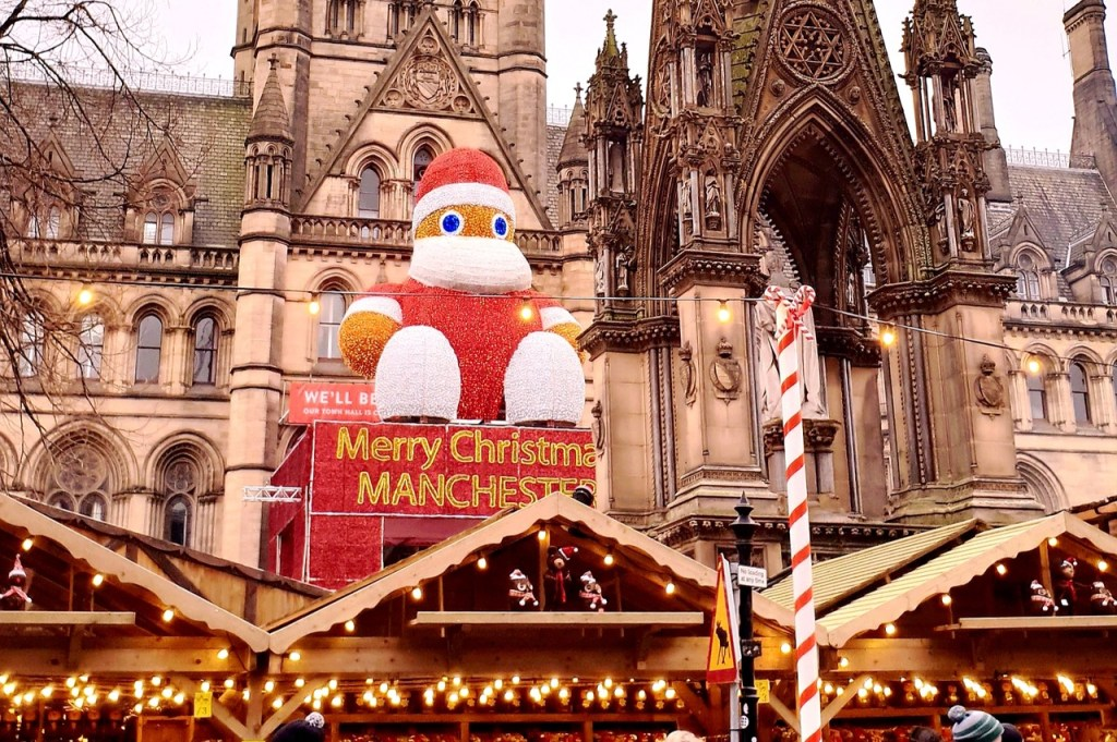 A large Christmas display reading 'Merry Christmas Manchester' in front of a cathedral during the Christmas markets.  In the foreground you can see the roofs of vendor stalls adorned with Christmas lights.