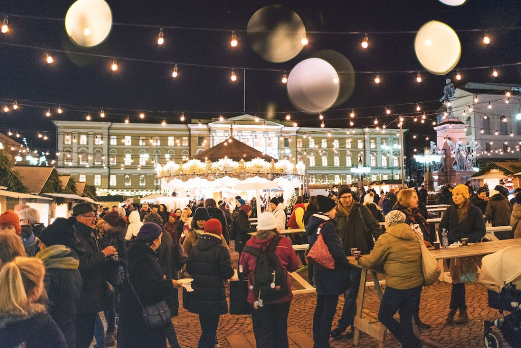 Many people gathering outside at night at Helsinki's primary Christmas market.  Strung lights and white globes are hanging from above.