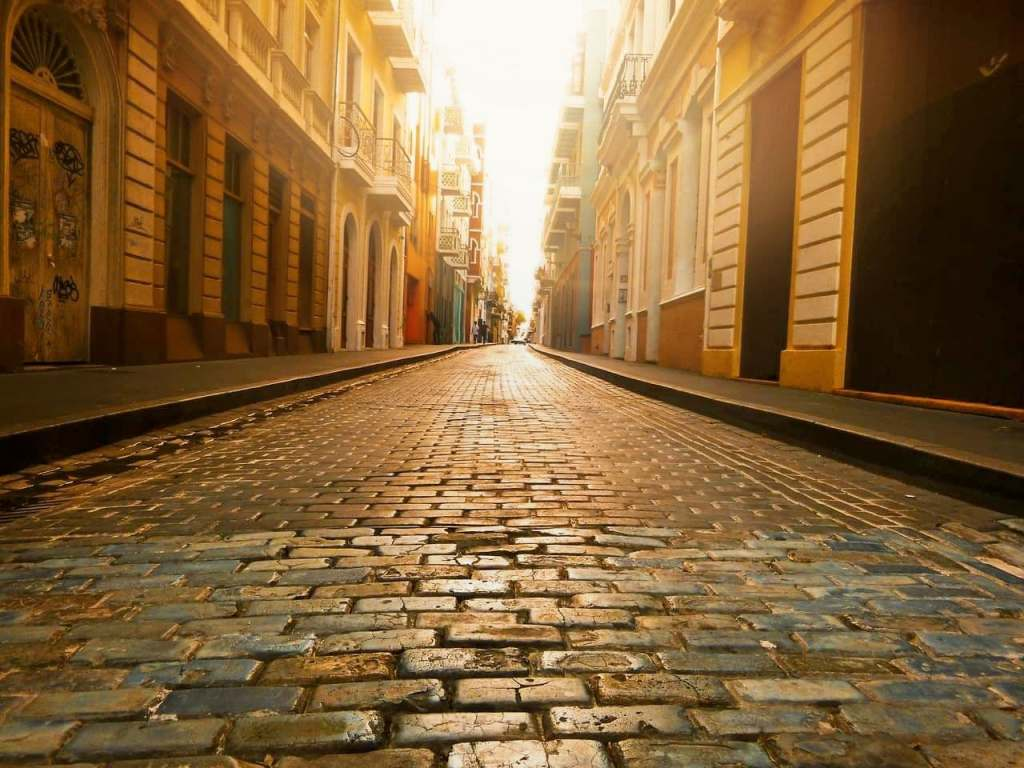 Light shining on cobblestone street in Europe.