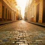 Light shining on cobblestone street in Europe.
