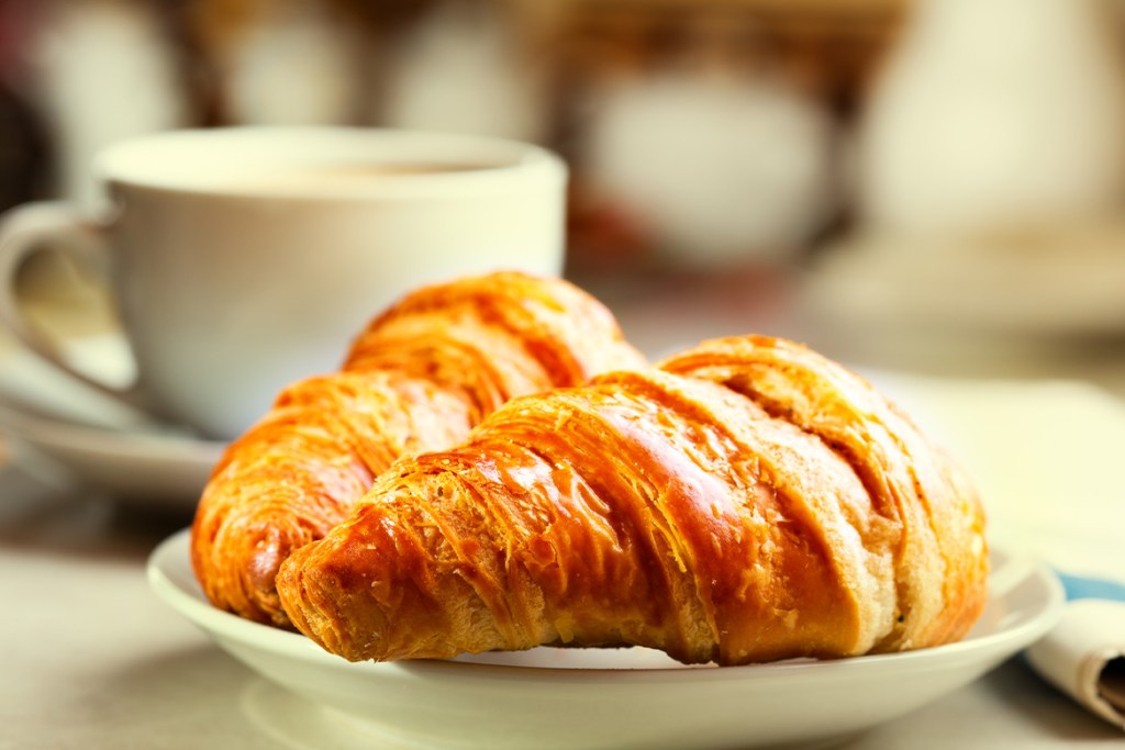 Close-up of two croissants on a side dish with a coffee cup in the backgound out of focus.