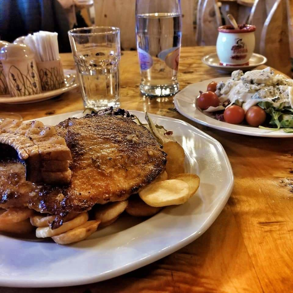 Hearty pork dish alongside a salad with tomatoes and white dressing on a table in Budapest.