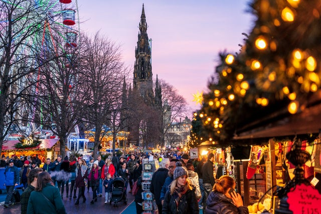 Visitors and shoppers walking around the many stalls at the Edinburgh Christmas Market.  The ferris wheel is visible in the background during sunset.