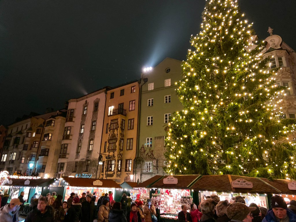 A row of buildings are in the background of the wooden Christmas market stalls in Innsbruck, Austria.  A large, lit Christmas tree is to the right.